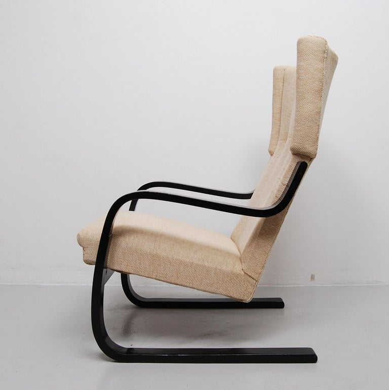 A wingback lounge chair model 401 designed by Alvar Aalto for Artek, Finland, 1933. Black lacquered birch frame and earlier reupholstered in a two-tone beige wool fabric in very good condition. A scratch after a repair is seen on the right hand leg,