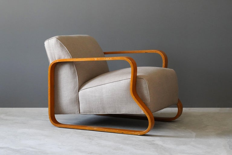 A rare and early lounge chair, designed by Alvar Aalto. Distributed to the UK and internationally by Finmar Ltd. Executed in bent birch, reupholstered in brand new high-end fabric. 