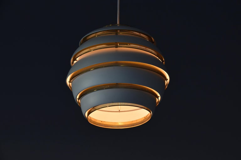 An early organic Beehive ceiling lamp / pendant designed by Alvar Aalto in 1953 and produced by Valaistustyö Ky, Finland. Height adjustable. As illustrated in images, lamp produces a soft glow diffused by the brass grills.   Interior rod impressed
