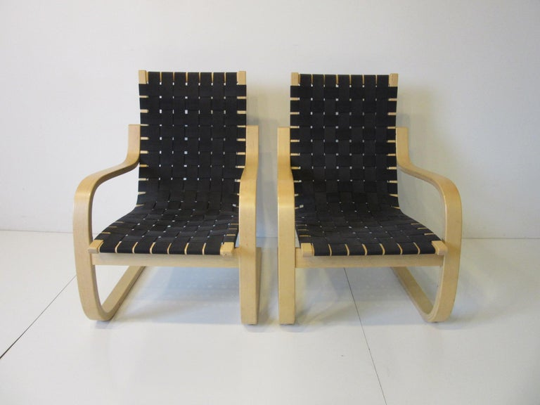 A pair of sculptural bent birch wood framed lounge chairs with black woven strap seating by Finish designer Alvar Alto. A very comfortable Classic form with ergonomics in mind, retains the label from the importer ICF manufactured in Finland by Artek