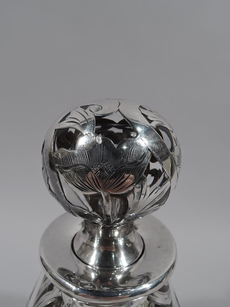 Art Nouveau clear glass decanter with engraved overlay. Made by Alvin in providence, circa 1910. Rectilinear baluster with short neck and flat rim. Ball stopper with short plug. Overlay in form of blooming stem flowers. Fully marked and numbered