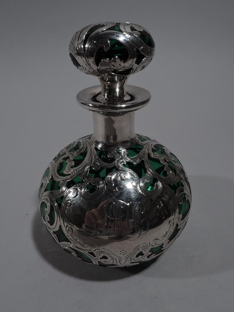 Art Nouveau green glass perfume bottle with silver overlay. Made by Alvin in Providence, circa 1900. Globular with short neck and everted rim. Squat ball finial with short plug Silver overlay in form of dense and interlaced scrollwork. Armorial