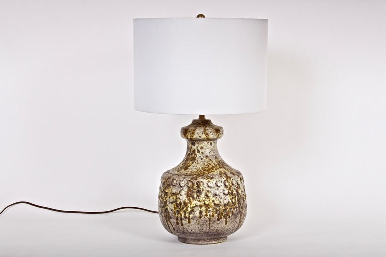 Italian modern Alvino Bagni textured bright earthen drip glazed ceramic bedside lamp. Featuring a three dimensional handcrafted squat body with raised button accents. With speckled and reflective coloration in beige, white, brown, coffee and pale