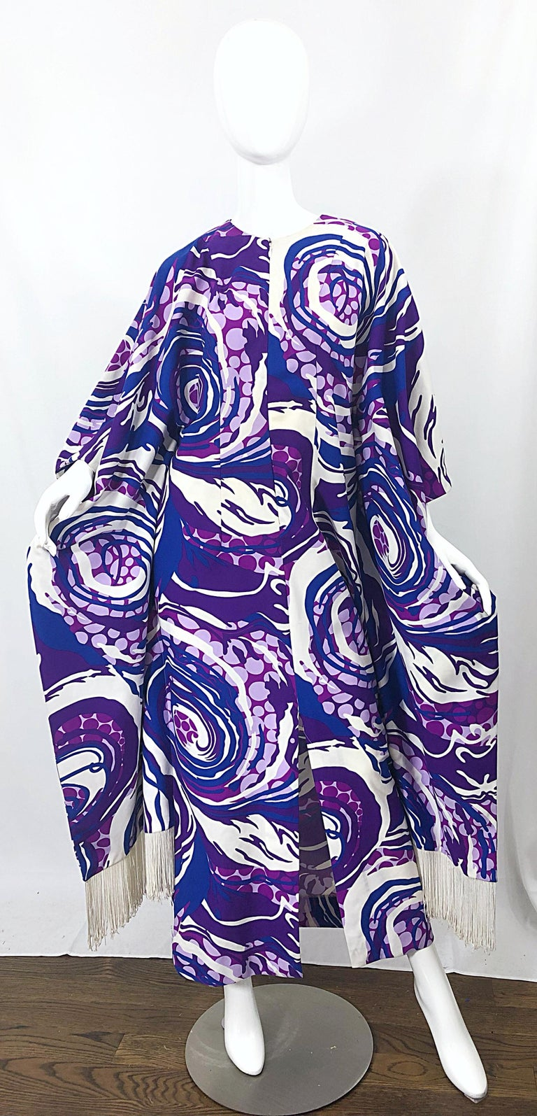 Amazing 1970s purple, blue and white swirl abstract print fringed kaftan / maxi dress! Features white fringe at each side hem. Hidden zipper up the front. In great condition.  Can fit most sizes, due to the natural fit of a caftan