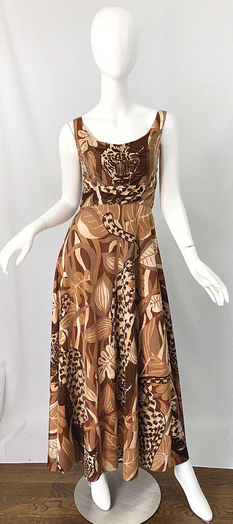 Channel your inner Joe Exotic from Tiger King in this 1970s FUTURA COUTURE leopard print sleeveless leopard print jersey maxi dress! Features leopard prints throughout in brown, ivory, white, terra cotta, and tan throughout. Tailored bodice with a