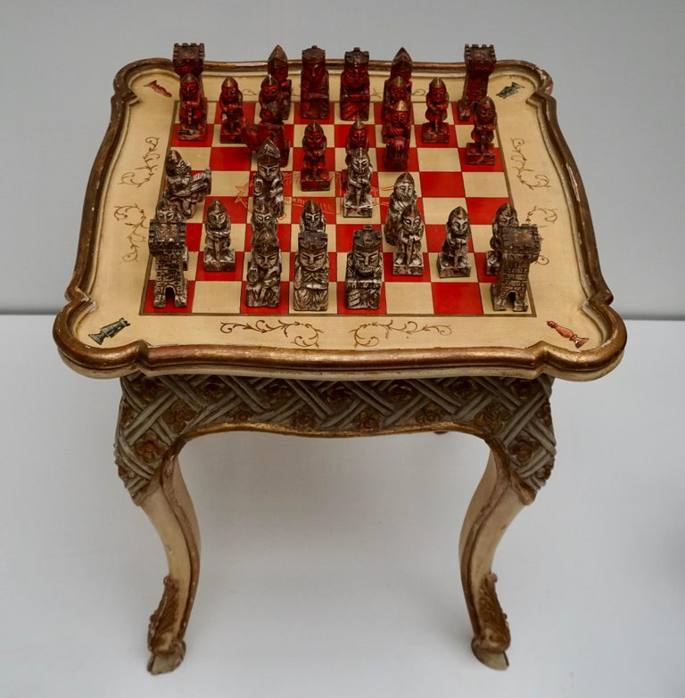 Rare Italian chess table set from early 20th century in carved, lacquered, gilded and hand painted wood with very pleasant floral decorations.   Measures: Height 79 cm. Width 69 cm.