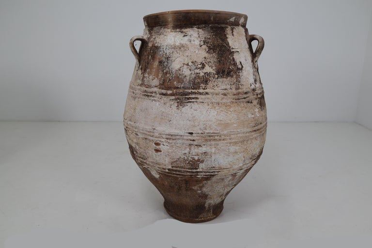A large vintage three-handled painted terracotta urn from early 20th century Greece, with white finish and rounded belly. Picture this large 1900s urn in its former life, on a shaded terrace under an olive tree overlooking the Mediterranean Sea in