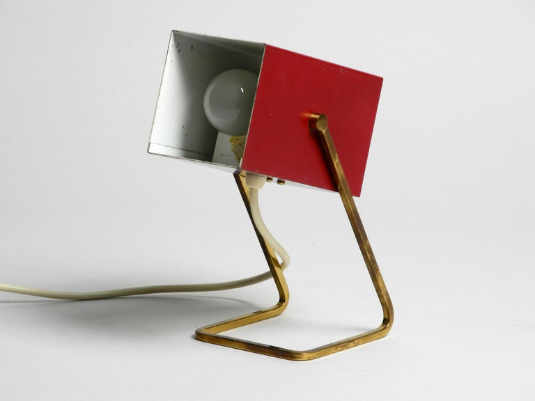 Stunning Kaiser Mid-Century Modern metal bedside lamp. Painted red outside and white inside. Very rare to find with angular shade, which is steplessly movable. Very high quality, entirely made of metal. Good vintage condition without damages to