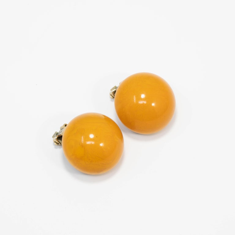 A pair of stylish vintage bakelite earrings. Each features an amber butterscotch yellow bakelite button set on brass-tone clip on hardware.  Circa early to mid 1900s.
