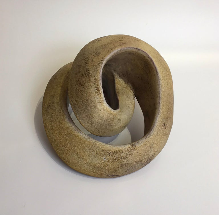 This dynamic coil form object is hand created and fired. The artist achieves the beautiful yellow amber matte surface by sandblasting the sculpture after removing it from the kiln.  Jerilyn Virden Amber Recoil Handbuilt earthenware, hollow