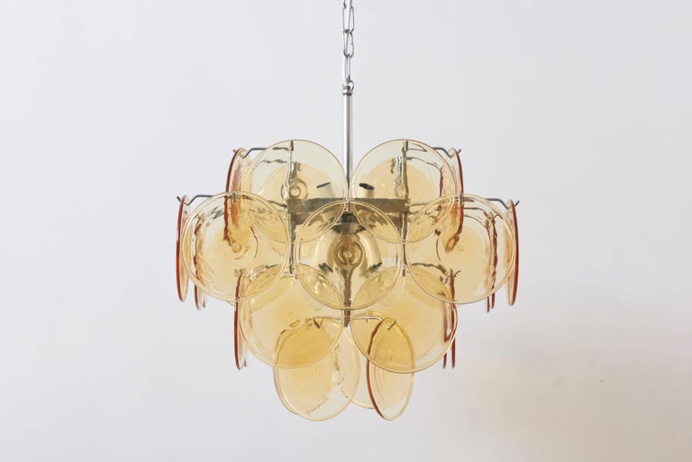 Midcentury colorful Italian chandelier by Vistosi with four tiers of 32 amber colored glass discs and chrome hardware.
