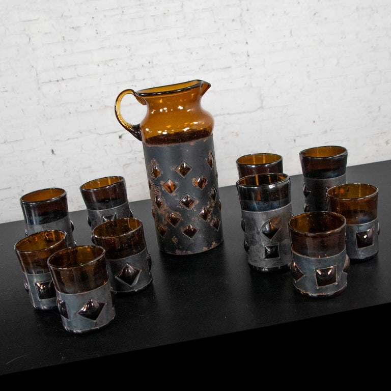 Incredible set of 11 pieces of imprisoned glass brutalist modern Mexican glass cocktail set including 10 tumblers in two sizes and a cocktail pitcher all in amber recycled bottle glass caged by blackened metal bands. Designed and made by Filipe