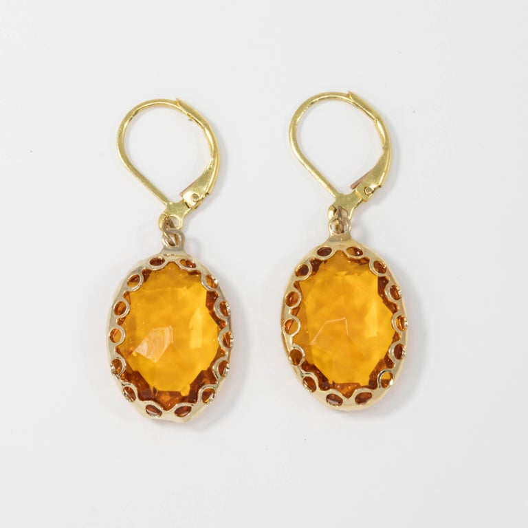 A pair of bright amber-yellow crystal dangling earrings. Each crystal is set in a decorative gold tone bezel. Lever back hook finding.  Circa mid 1900s