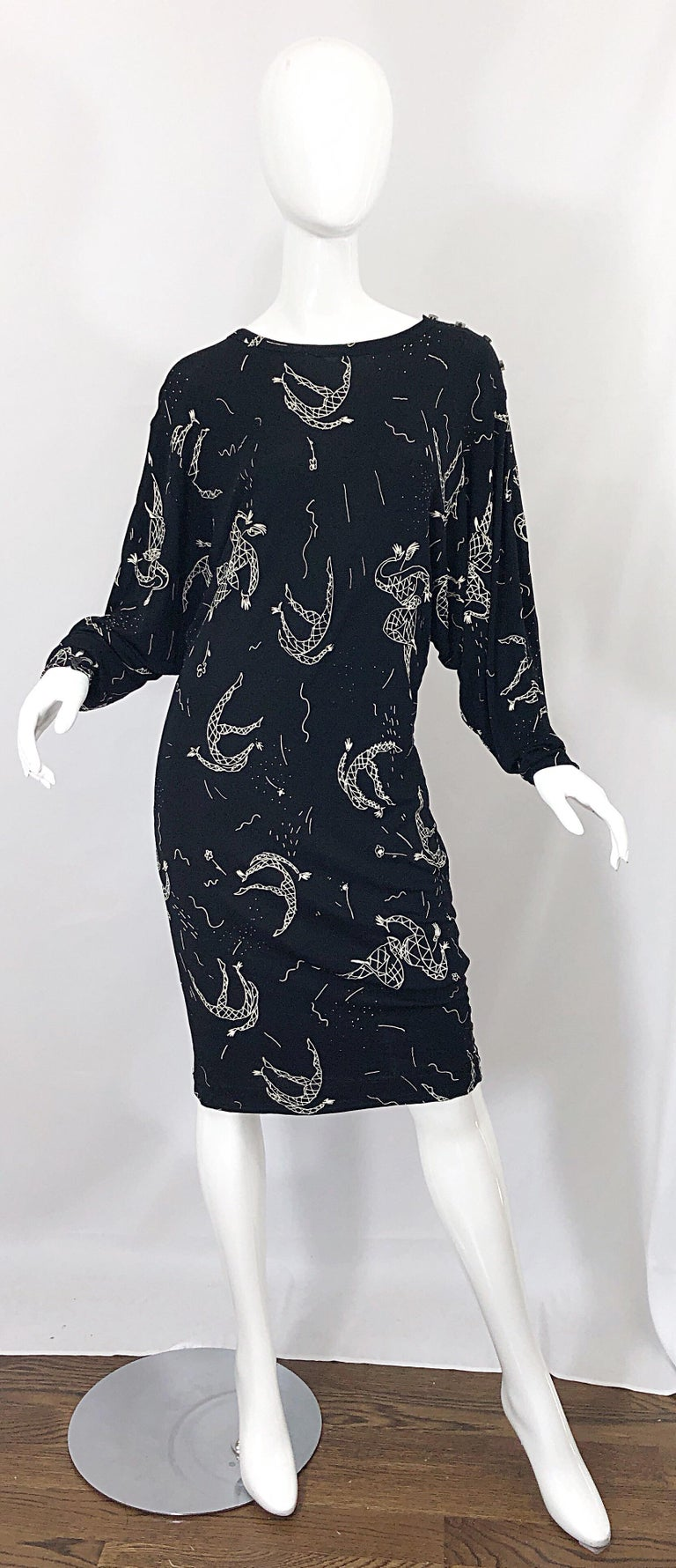 Extraordinary vintage mid 1980s AMEN WARDY black and white hand painted harlequin novelty print jersey dress! Features a stretch rayon jersey and dolman sleeve that can accomodate an array of sizes. Buttons at top left shoulder. Great belted or