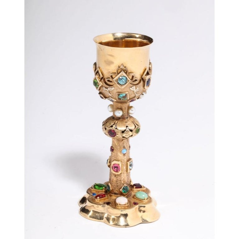 An American 14-karat yellow gold and semi precious stone miniature chalice cup, circa 1970.    Polished and brushed 14-karat yellow gold set with pearls, opal, jade, diamonds, and colored gem stones.    Measures: 4.5