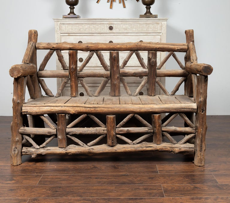 A large American rustic bench from the early 20th century, made of logs. Born during the second quarter of the 20th century, this wooden bench charms us with its rustic appearance and weathered patina. Made of logs arranged in geometric patterns and