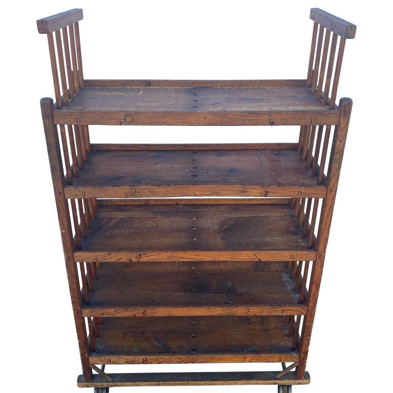 Industrial 5-tier wooden rolling storage rack on iron wheels.