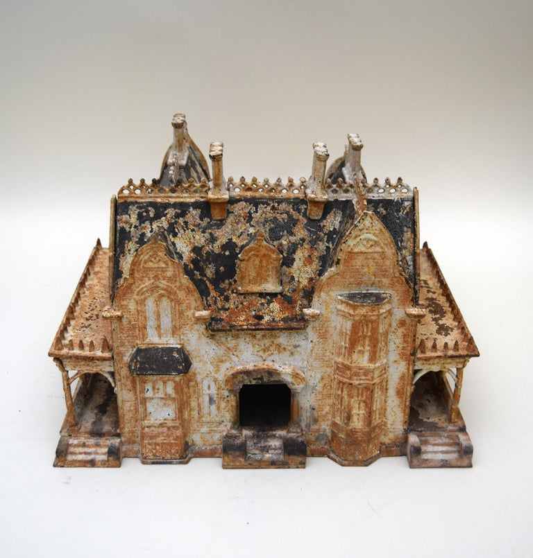 This charming 19th century Victorian birdhouse was modeled on the Neo-Gothic mansions that were then being built for the potential buyers of birdhouses. Cast in iron, it bears the name of its Rhode Island maker, the Miller Iron Company, and dated