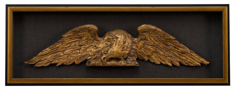 This is a pair of hand carved, American eagles, a beautiful matched architectural set. The pair was designed to be mounted over doorways or between columns. Each eagle is displayed with wings fully extended, one faces to the right, the other to the