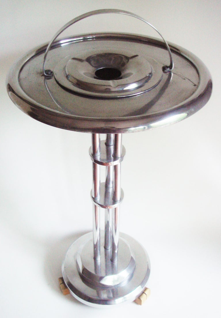 This stunning rare American Art Deco/Machine Age polished Aluminum floor standing ashtray/smoker's table stands on three butterscotch Bakelite feet. It looks as though it should be in Buck Roger's man cave. (Please see photo as it does have a