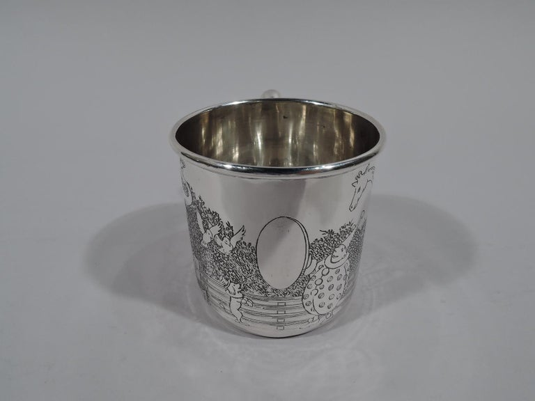 Art Deco sterling silver baby cup. Straight sides and c-scroll handle. Engraved circus animals with giraffe, elephant, and dancing dog. A clown holds up a funhouse mirror—a vacant frame for engraving the name of the big top's star attraction. Fully