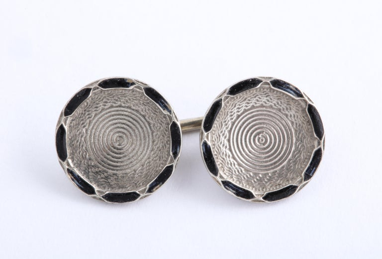 Circular pattern throughout contains black guilloche enamel decoration with alternating intersecting silver on rim with central concentric circles towards the center.  Raised Letters STERLING