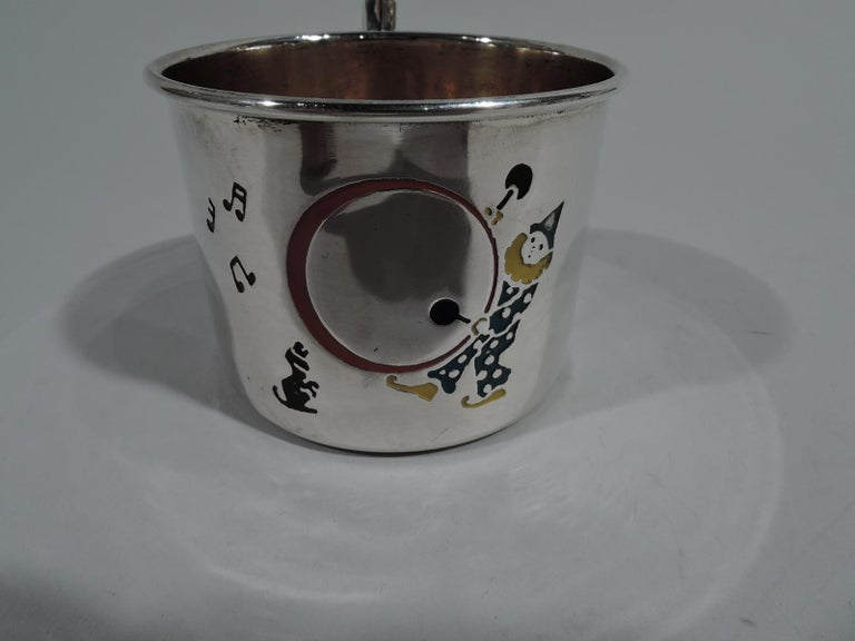 Novelty sterling silver baby cup. Made by Webster in North Attleboro, Mass, circa 1920. Straight sides and high-looping scroll handle. Enameled decoration: A clown pounds away with drumsticks, musical notes emanating to the tune of a very special