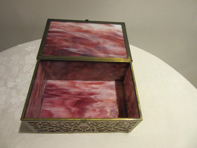 American Arts & Crafts cigar box with stained glass and pierced brass exterior. Made in the early 20th century in the United States. The box is standing on four tiny feet and is in great antique condition with age-appropriate wear and use. Some