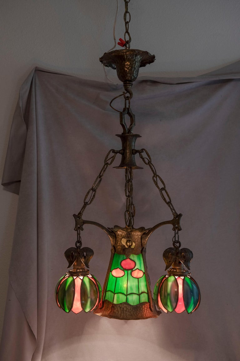This colorful quality little chandelier offers good light and wonderful aesthetics. The center section has a pretty floral pattern of leaded glass. The 3 accompanying shades are all bent glass into a floral shape. All the glass is original and with