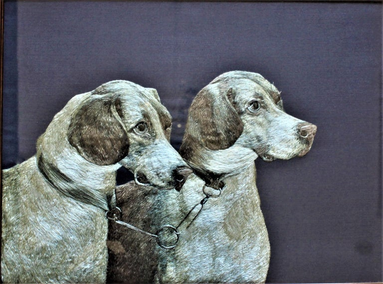 Presumed to having its origins in the United States and done in the Arts & Crafts period, this extremely intricate and realistic depiction of two hound dogs bridled together is done completely in various colors of silk thread. The faces and bodies