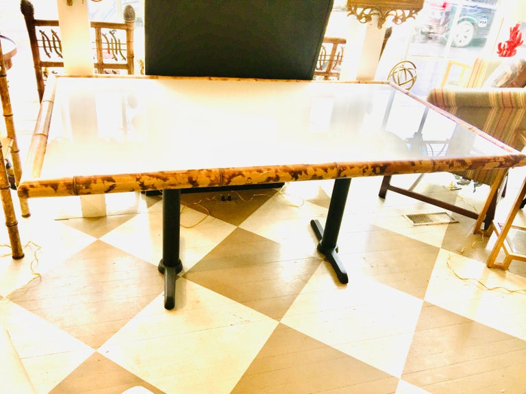 American center table, dining table, or writing table; Having a colorful thick bamboo Trim around a white wooden top on a metal base. There is a white milk glass on top of the wooden top setting in the bamboo trim. The two legs are charcoal black