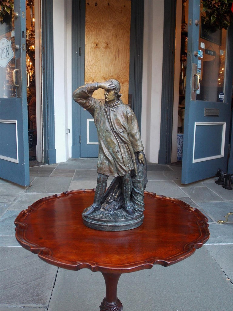 American bronze figural sea mariner bracing in wind against a rope piling and mounted to an oval molded edge base. Late 19th century.