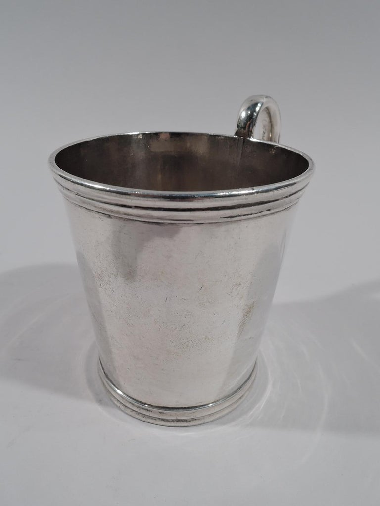"American classical coin silver baby cup. Made by Aaron Lufkin Dennison in Boston, circa 1850. Straight and tapering sides with reeded rim and foot, and high-looping handle. Marked ""A.L. Dennison & Co. / Boston / Pure Silver Coin"". Weight: 3.8 troy"