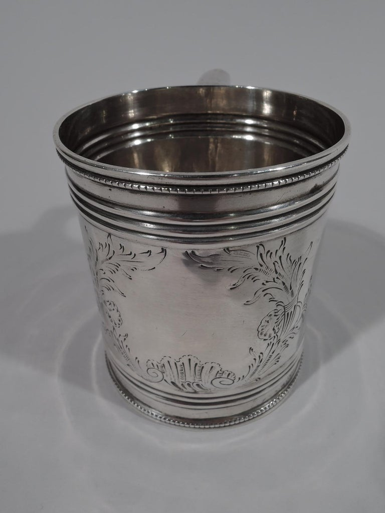 """Classical coin silver baby cup, drum-form with ribbing and beading. Engraved quivers, flowers, and leaves forming cartouche (vacant). Scroll-bracket handle. Marked """"G. W & H"""" for Gale, Woods & Hughes, a New York maker active circa 1833-1845. Weight:"""