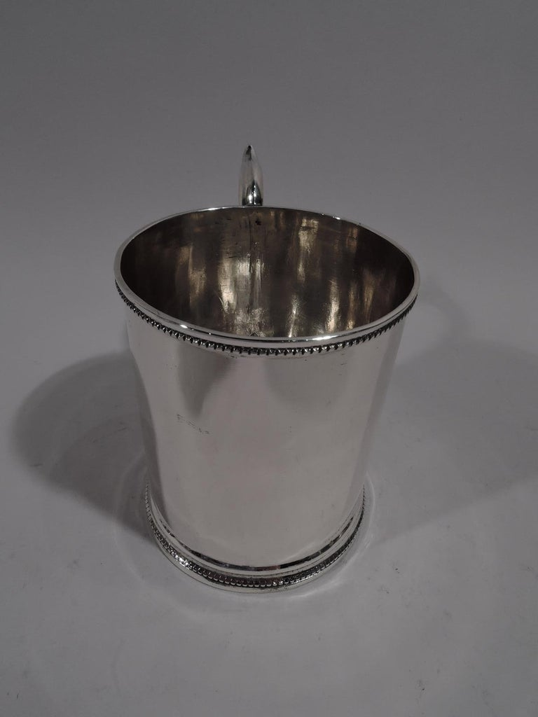"""American classical coin silver baby cup, circa 1850. Plain and straight sides with beaded rims and capped S-scroll handle. Lots and lots of room for engraving. Marked underside: """"Premium of the / Ills State Agl Society"""".  Overall dimensions: H 4 x"""