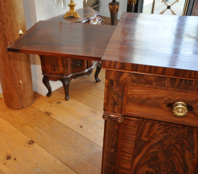 Book matched mahogany and mahogany veneered sideboard or serving cabinet of the period and influenced by Philadelphia Cabinetmaker, Antoine Gabriel Quervelle. Wonderfully carved columns and neoclassical bases, pull out slides for additional serving