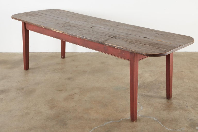 Rustic American country farmhouse harvest table or dining table crafted from reclaimed pine wood. The top is made from two 1 inch thick long planks having rounded ends. The base is painted barn red and is supported by square, tapered legs. Ample leg