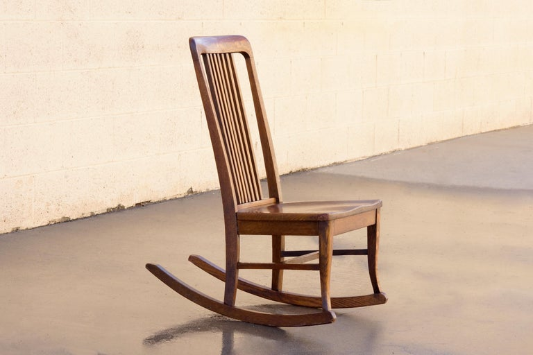 Petite size American craftsman rocking chair in solid oak. Wonderful and uncommon armless design with slatted high back . Excellent antique condition.