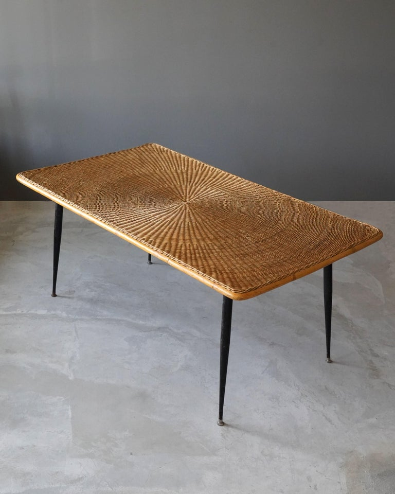 A dining table / dinette table / table. Designed and produced in America, 1950s. Woven rattan and lacquered steel.  Other designers of the period include Paul Frankl, Isamu Noguchi, George Nakashima, Edward Wormley, and Charles & Ray Eames.