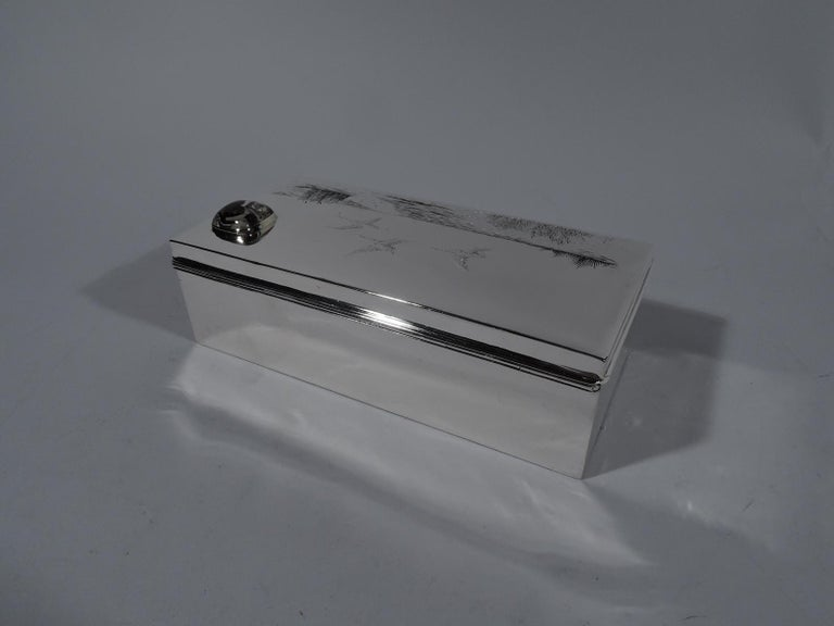 American Edwardian sterling silver box. Rectangular with straight sides. Cover hinged and gently curved. On top is chased and engraved hunt scene heightened with enamel: Lapping water, swaying grasses and cattails, and ducks flying overhead. In