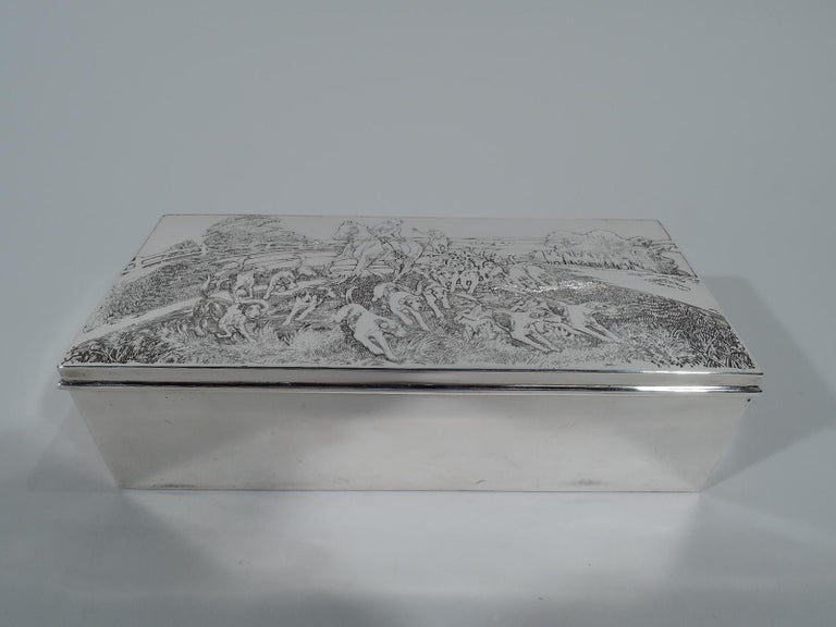 American Edwardian sterling silver box with hunt motif. Rectangular with straight sides and hinged cover. On cover is dense tableaux with hounds in pursuit followed by a mounted hunter who looks back at another wielding a whip. Box interior