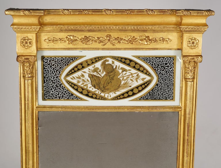This Federal period giltwood pier mirror, dating to circa 1820, is designed in the architectural style. It features an elegant projecting crest molding with applied classical ornaments and rosettes above an églomisé panel with a classical motif.
