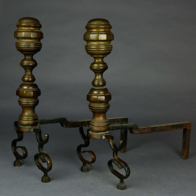 A set of American Federal Philadelphia style brass fireplace andirons offer brass beehive form with faceted elements, iron firedogs and raised on scroll form feet, circa 1850  ***DELIVERY NOTICE – Due to COVID-19 we are employing NO-CONTACT