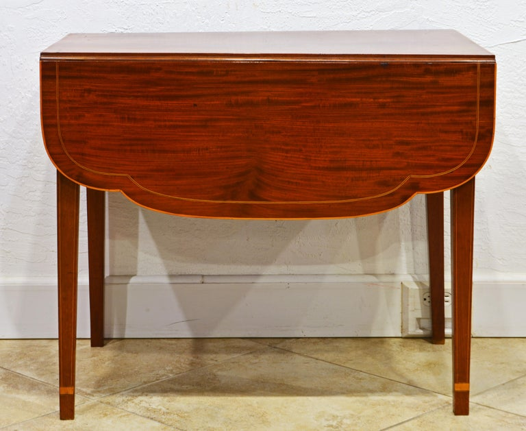 This distinguished American satinwood inlaid mahogany Pembroke table features a string inlaid top above a single drawer resting on square tapering inlaid legs accented by satinwood bands near the ends. The inlaid drop leaves have shaped corners and