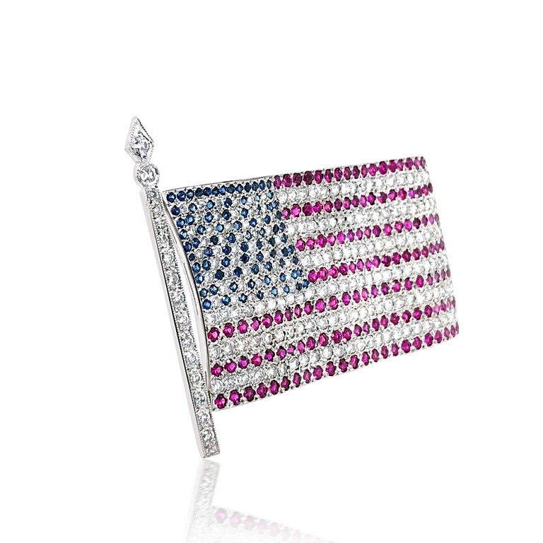 This American flag brooch features about 178 round diamonds size ranging from 0.025 to 0.01cts cumulatively weighing approx. 4.2cts. The stripes on the flag contain 135 round rubies cumulatively weighing approx. 4.1ct, and the stars on the flag
