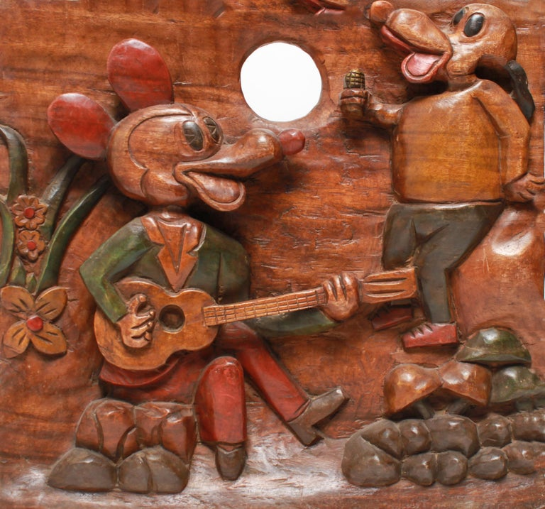 American Folk Art carved and painted cartoon wood plaque featuring a Mickey Mouse figure playing the guitar and a Goofy character in the background, surrounded by flora and rocks. The piece is in good vintage condition.