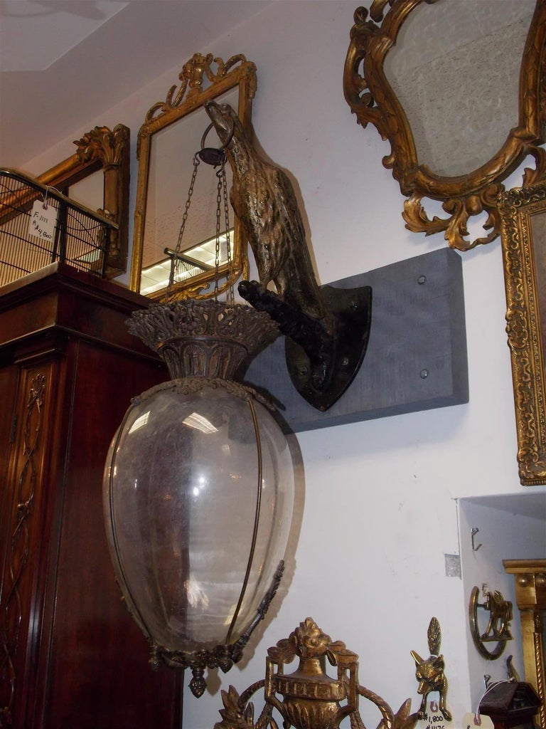 American hanging Apothecary show globe with a mounted cast iron painted and gilded eagle. Globe was filled with a colorful green or red liquid to warn a largely illiterate public of a plaque or to signal all was well. Mid-19th century.