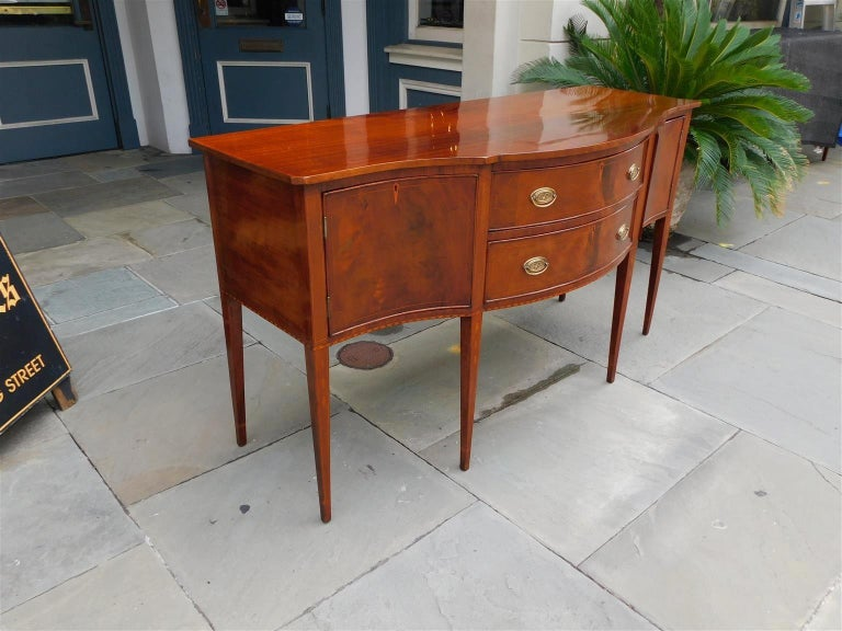 American Hepplewhite mahogany serpentine sideboard with two centered satinwood string inlaid drawers, flanking hinged cabinets, checkering inlaid border, graduated bell flower inlays, diamond inlaid escutcheons, original oval eagle star brasses,