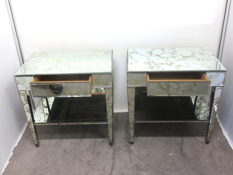 American Hollywood Regency pair of 1950s veined mirrored nightstands. Each nightstand has one center drawer and a bottom shelf. Very good vintage condition with bubble damage on one small section on the top of one nightstand. Black marks on 4 of the