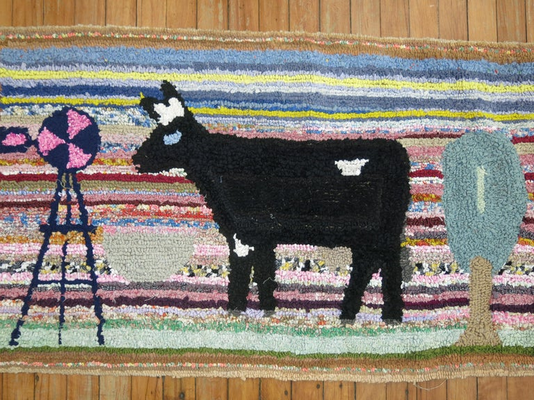A handmade American hooked rug from the early part of the 20th century depicting a black cow. Condition is really nice. No stains, no tears, has been professionally cleaned. Backed with blue fabric.